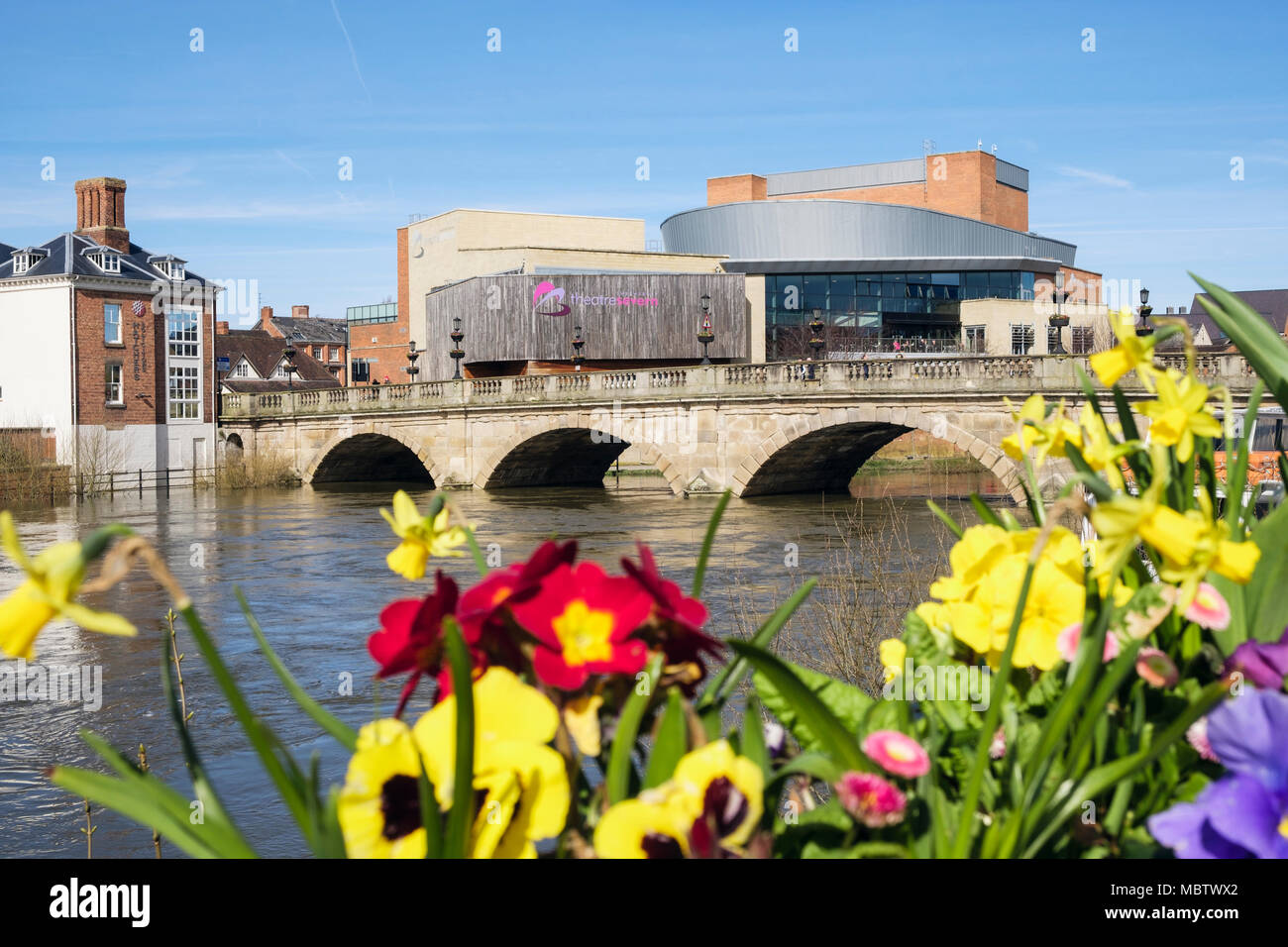The Welsh Bridge over the River Severn with TheatreSevern beyond spring flowers in flower boxes. Shrewsbury, Shropshire, West Midlands, England, UK - Stock Image