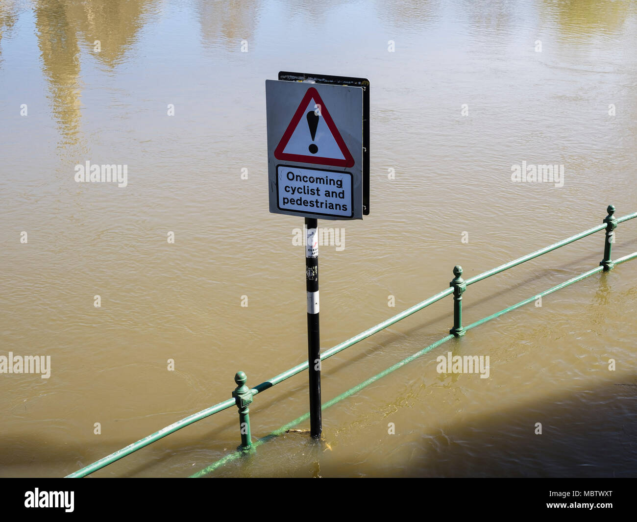 Red triangular road sign in high spring flood water level on track by River Severn. Shrewsbury, Shropshire, West Midlands, England, UK, Britain - Stock Image