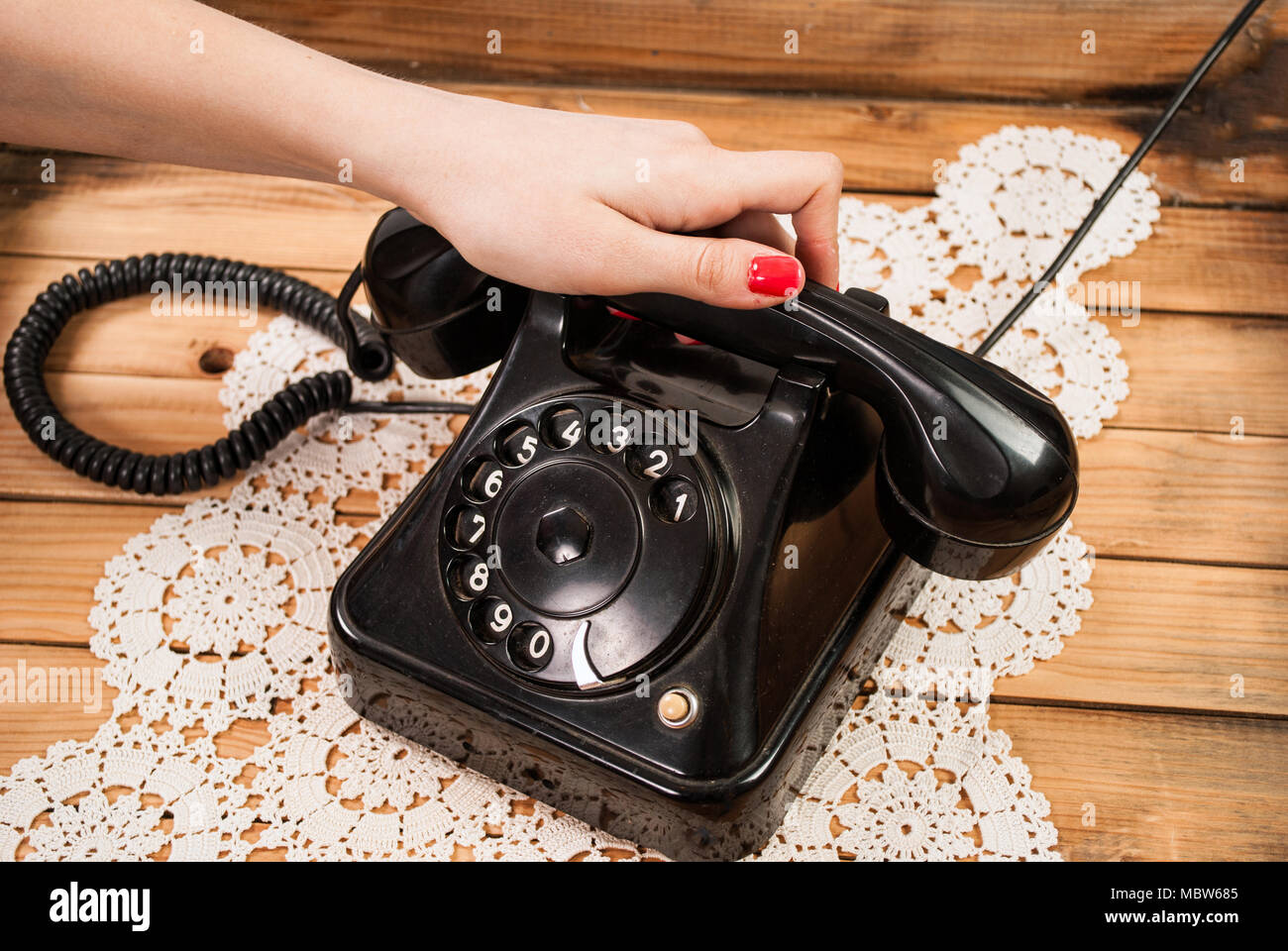 Girl hand holding old telephone headset on lace tablecloths and wooden background - Stock Image