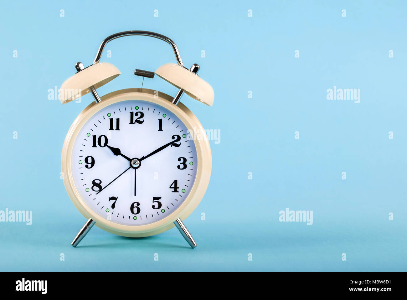 Old retro clock on blue background and space for text and editing - Stock Image
