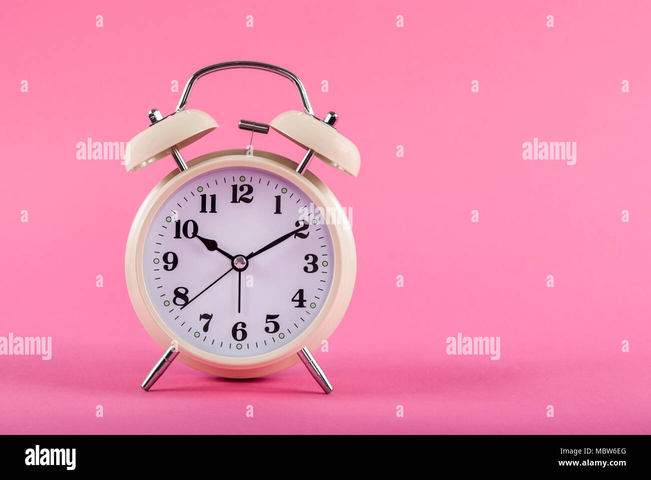 Old retro clock isolated on pink background and space for text - Stock Image
