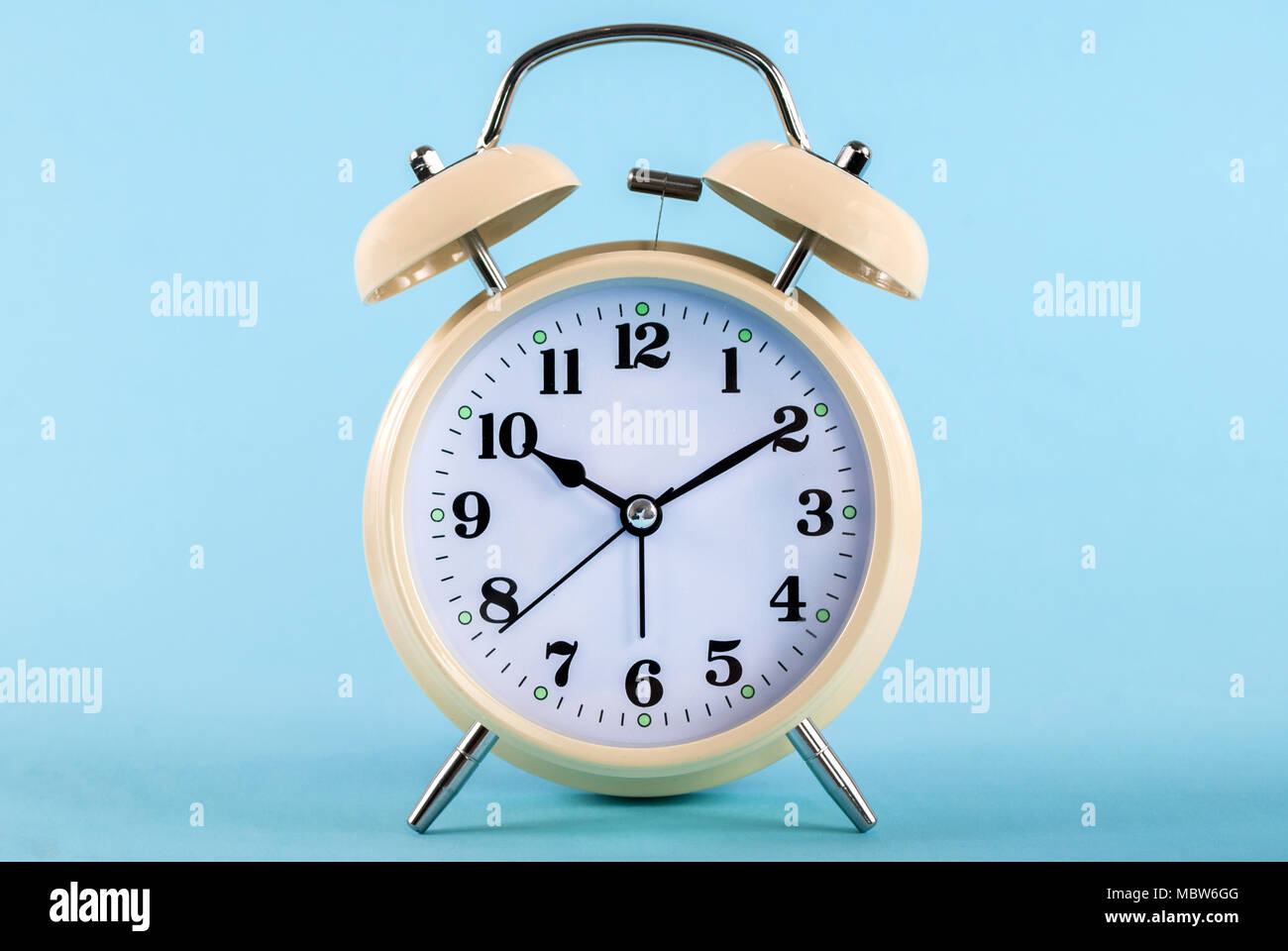 Old retro clock isolated on blue background - Stock Image