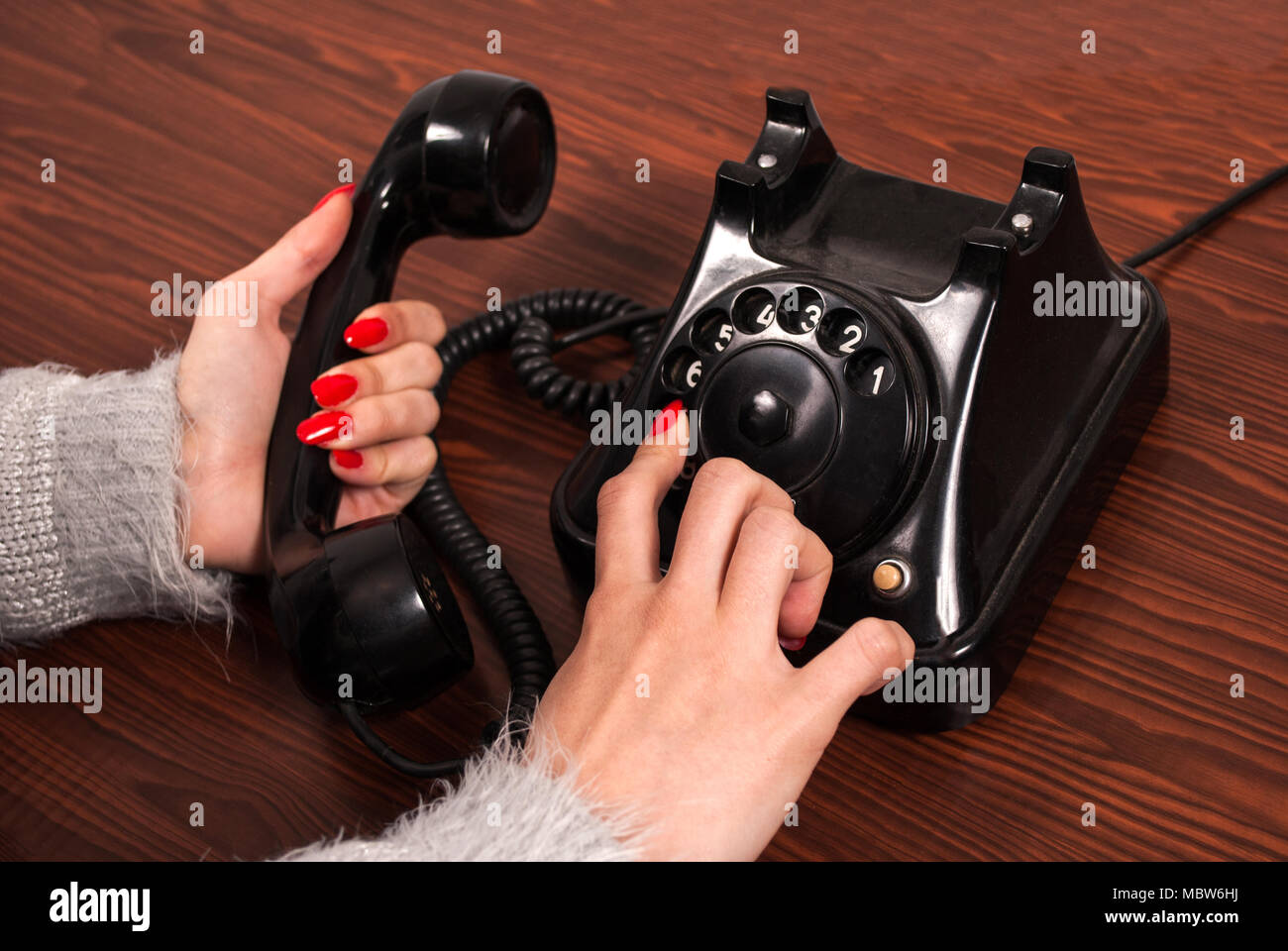 Woman hand and old phone on wooden desk. Finger dial telephone numbers - Stock Image