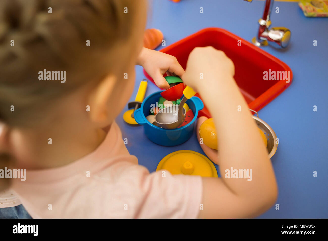toddler girl playing toy kitchen. She cooking soup - Stock Image