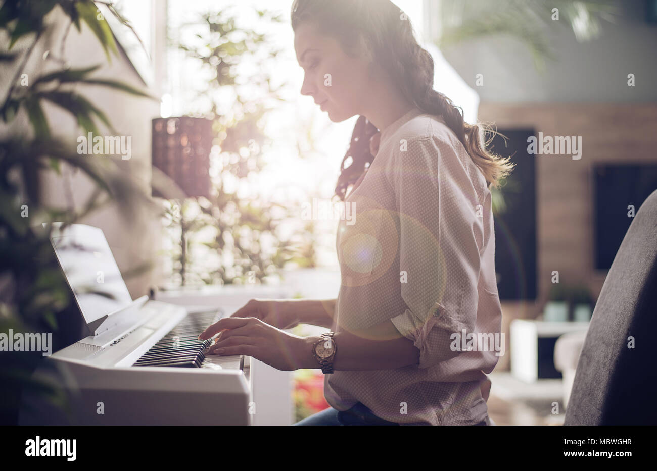 Pretty young lady playing the synthesizer - Stock Image