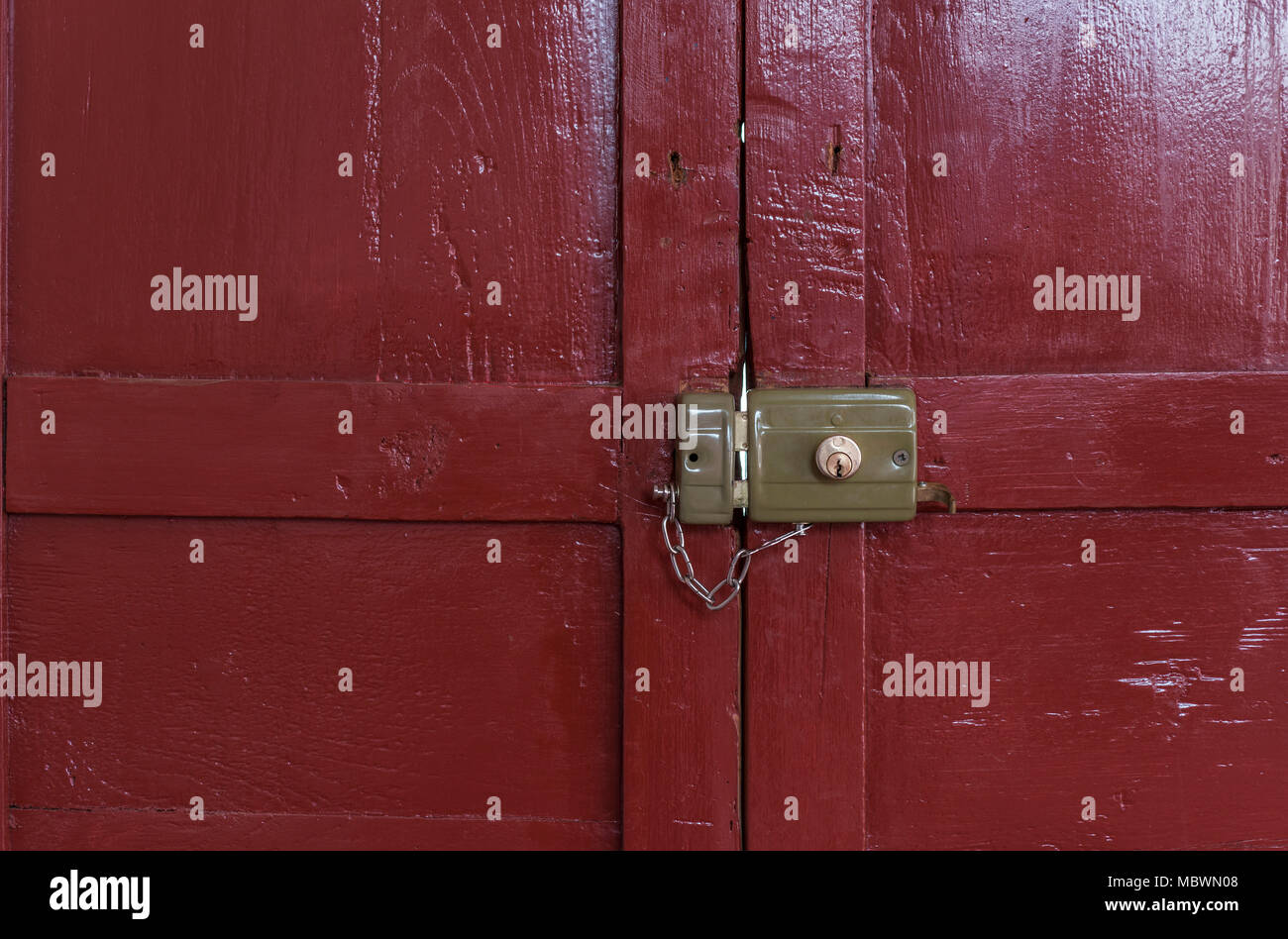old lock locked with its chain seen from inside an old door painted ...