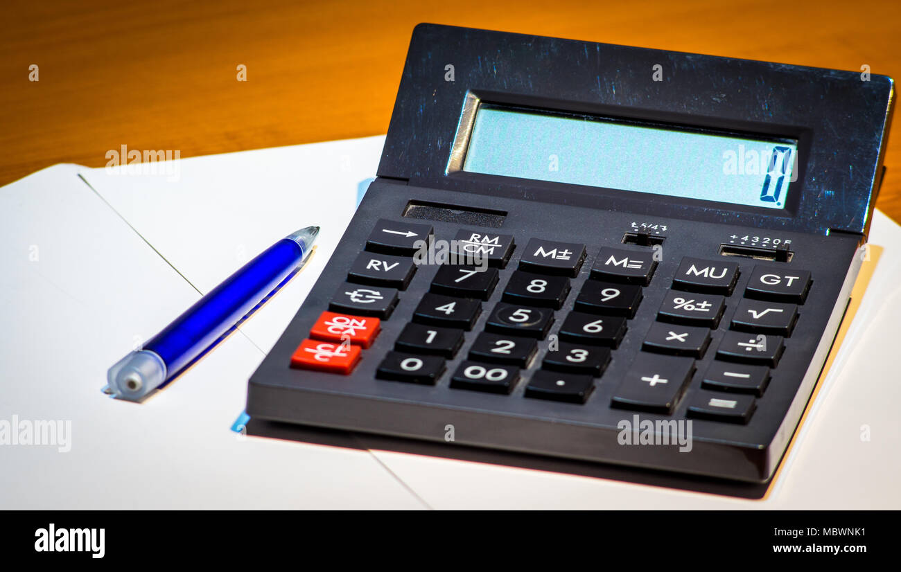 Black calculator with 0 on display and a pen - Stock Image