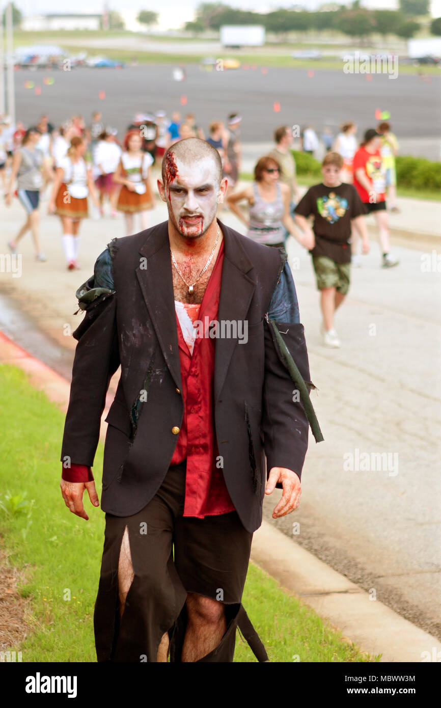 A male zombie wearing a tattered suit, emerges from the crowd after chasing runners in the Atlanta Zombie 5K Run, on June 8, 2013 in Hampton, GA. - Stock Image