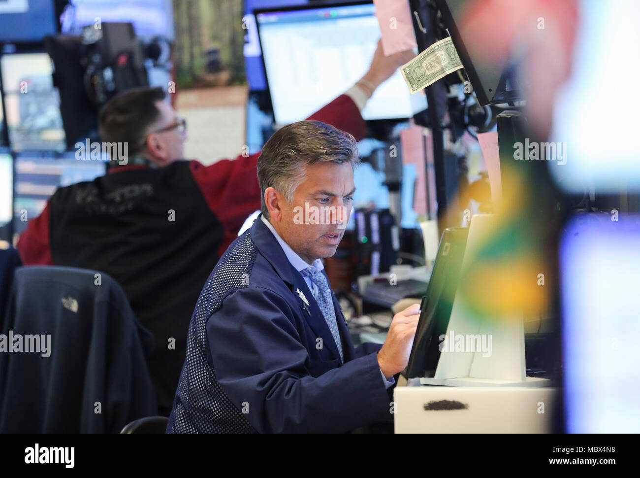 New York, USA. 11th Apr, 2018. Traders work at the New York Stock Exchange in New York, the United States, April 11, 2018. U.S. stocks closed lower on Wednesday. The Dow decreased 0.90 percent to 24,189.45, and the S&P 500 erased 0.55 percent to 2,642.19, while the Nasdaq lost 0.36 percent to 7,069.03. Credit: Wang Ying/Xinhua/Alamy Live News Stock Photo