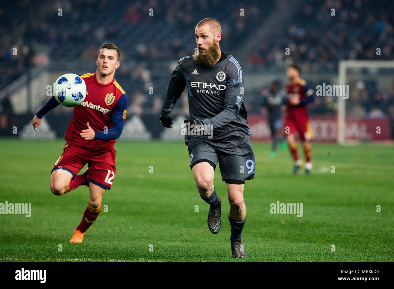 Bronx, New York, USA. 11th April, 2018. Jo Inge Berget (9) of NYCFC chases down a ball against Brooks Lennon (12) of Real Salt Lake during the second half of the game. NYCFC won 4-0. - Stock Image