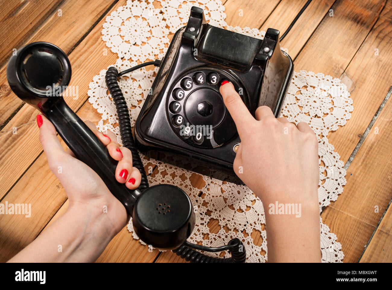 Woman hand dialing number on old phone on lace tablecloths and wooden background - Stock Image