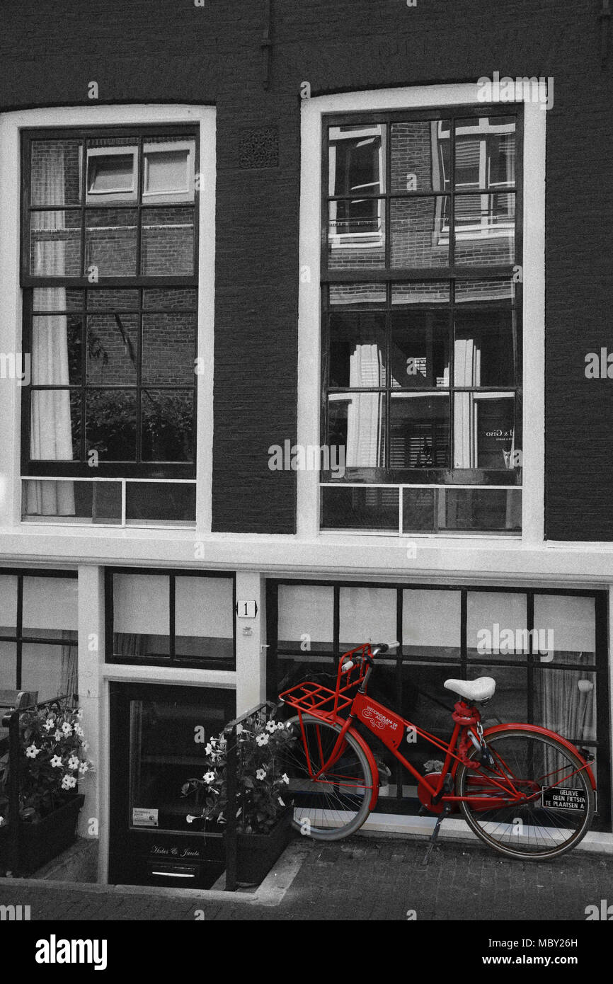 Red bike parked outside a Dutch house, Amsterdam, the Netherlands - Stock Image