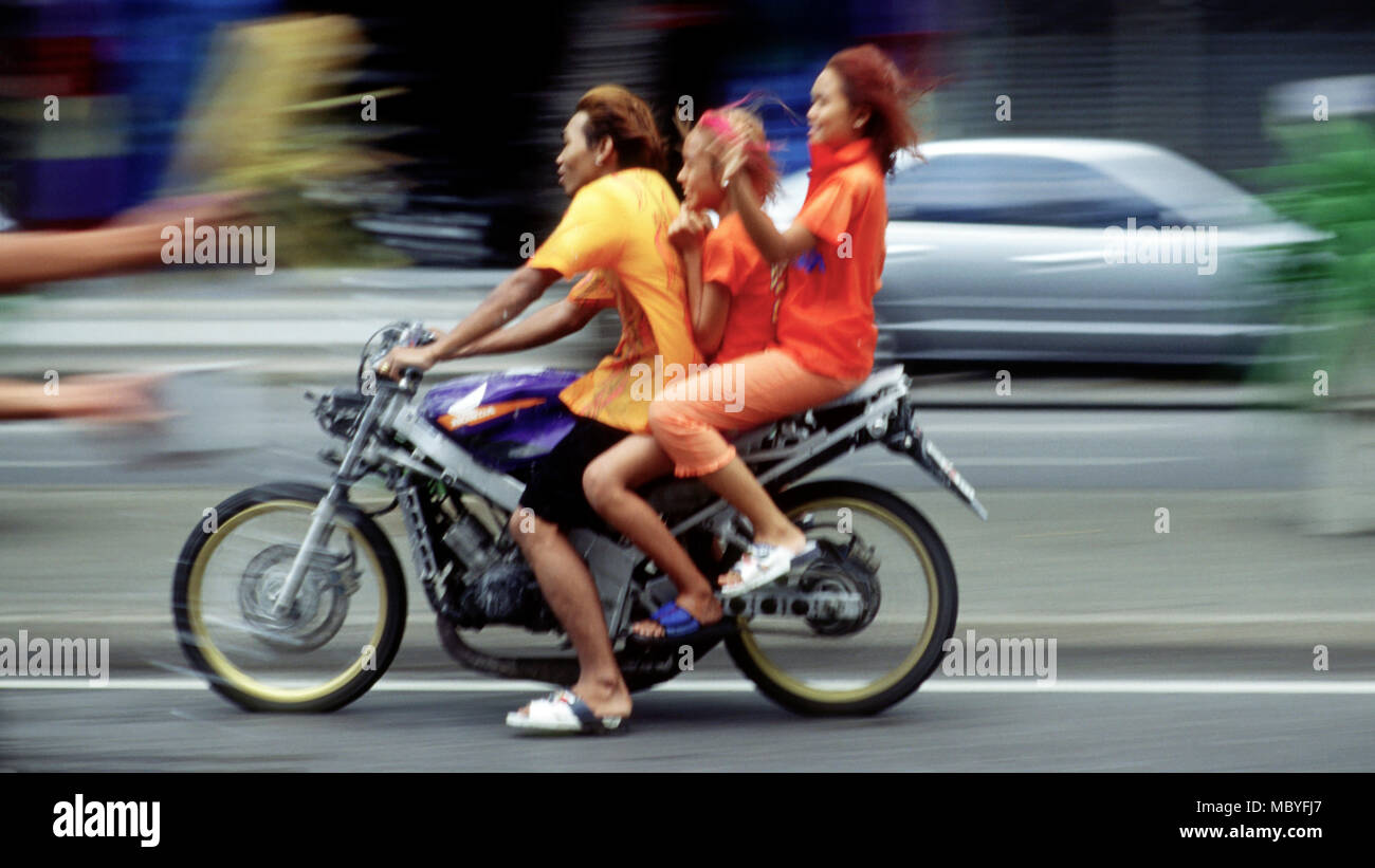 Passengers on a passing motorbike are splashed with water during Songkran, 2001 in Bangkok, Thailand. - Stock Image