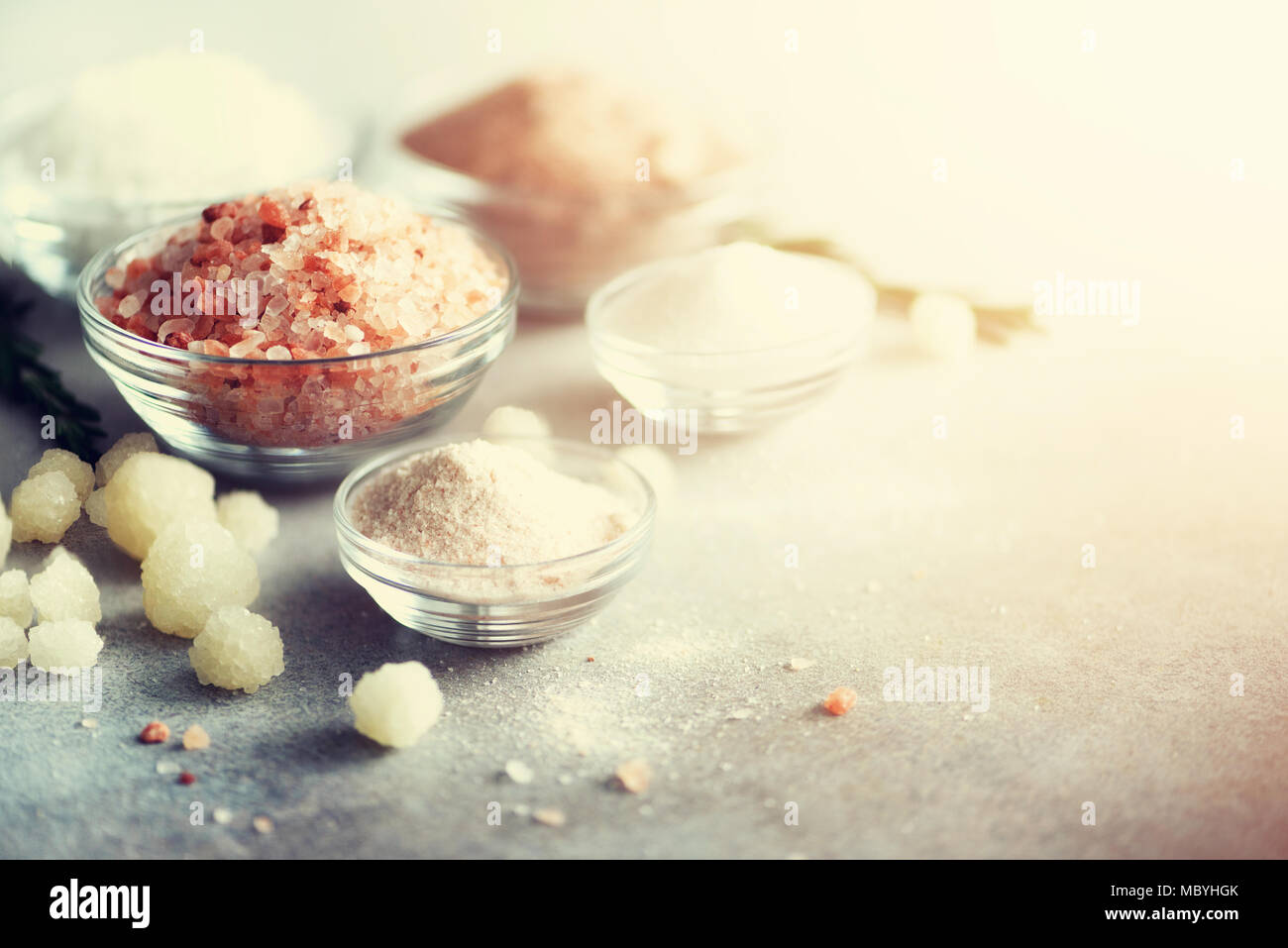 Mix of different salt types on grey concrete background. Sea salts, black and pink Himalayan salt crystals, powder, rosemary. Salt crystal balls from Dead sea. Copy space. Toned sunlight effect - Stock Image