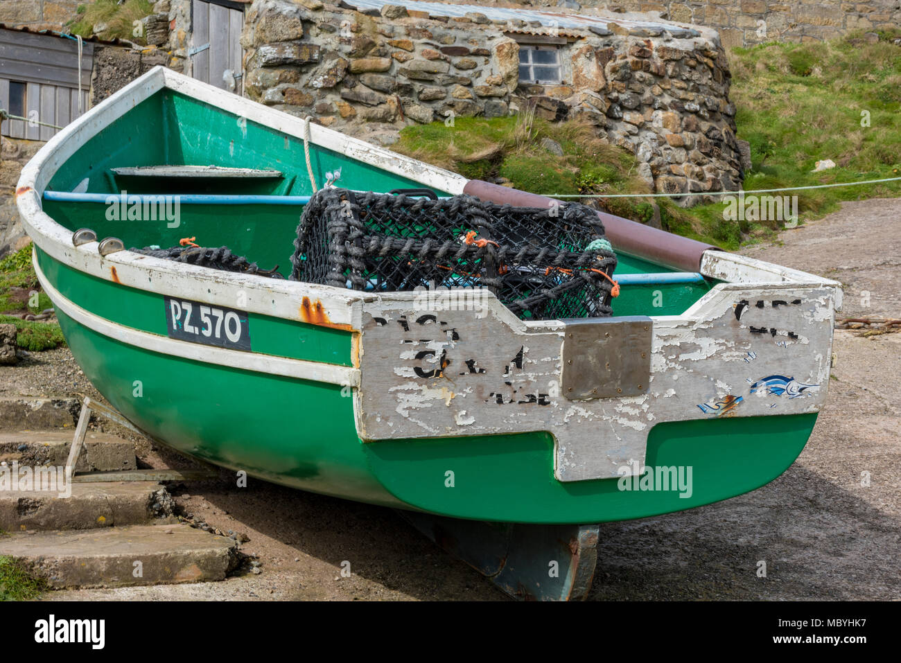 A small colourful fishing boat on a slipway on the Cornish coast at cape cornwall near st just on the penwith area lizard peninsular. Fishermen boat. - Stock Image