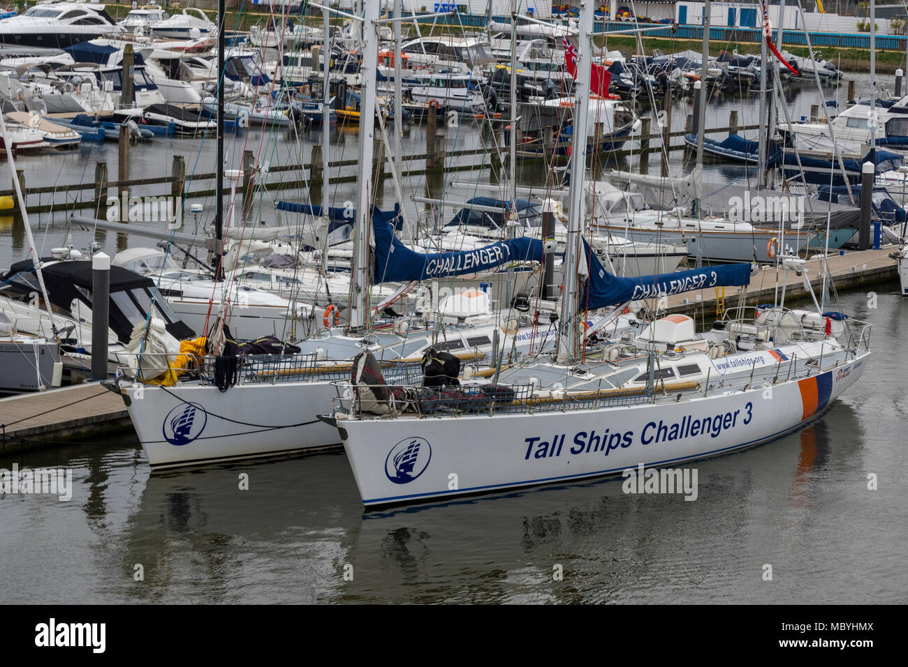 tall ships challenge yachts alongside at the marina or harbour at Lymington river in the new forest. Sailing adventures and instruction on large boats - Stock Image