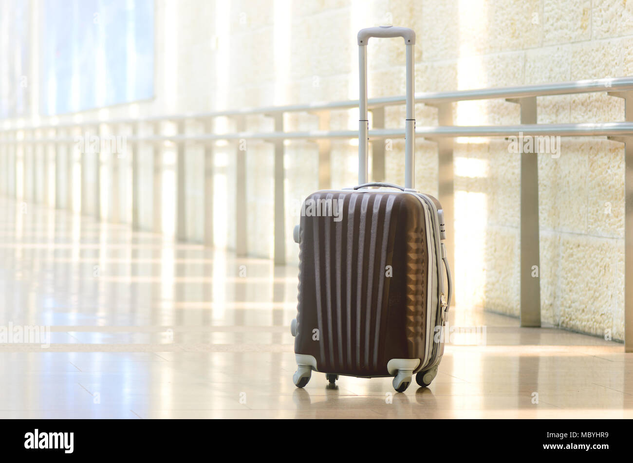 Packed travel suitcase, airport. Summer holiday and vacation concept. Traveler baggage, brown luggage in empty hall interior. Copy space - Stock Image