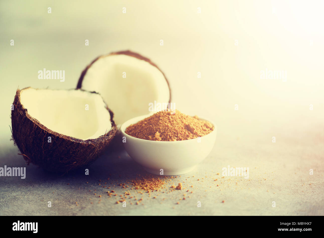 Coconut palm brown sugar and half of coconut fruit on grey concrete background. Copy space - Stock Image