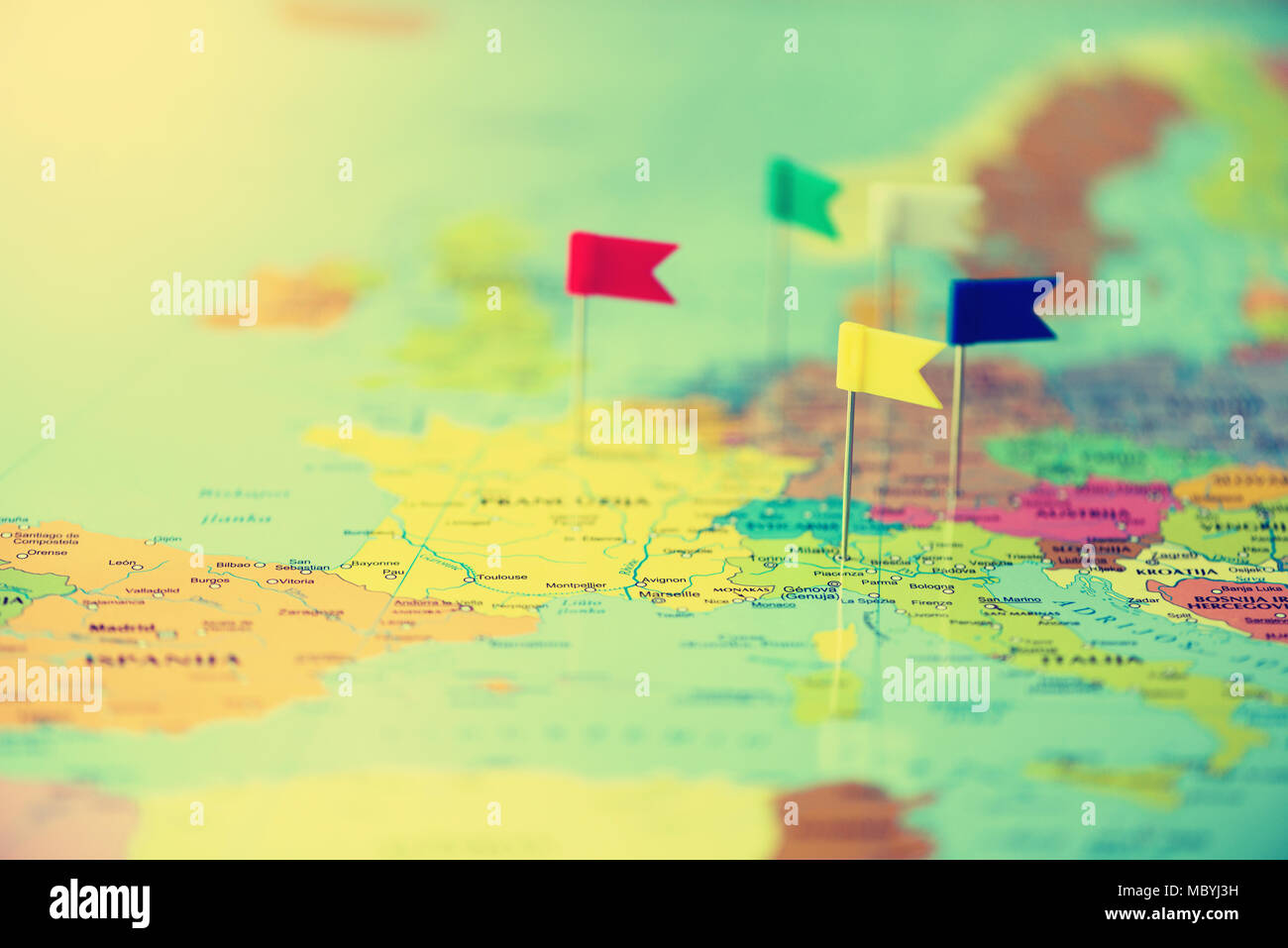 Colored flags, pushpins, thumbtack pinned on map of europe. Copy space, travel concept - Stock Image