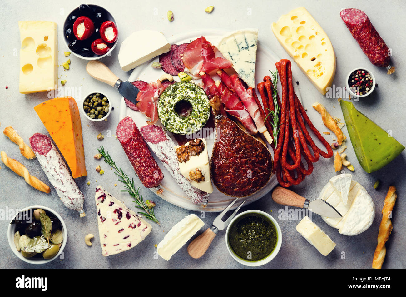 Cutting board with cold smoked meat, prosciutto, salami, assortment of cheeses, bread sticks, capers, olives on grey stone background. Cheese and meat appetizer. Top view, copy space, flat lay - Stock Image