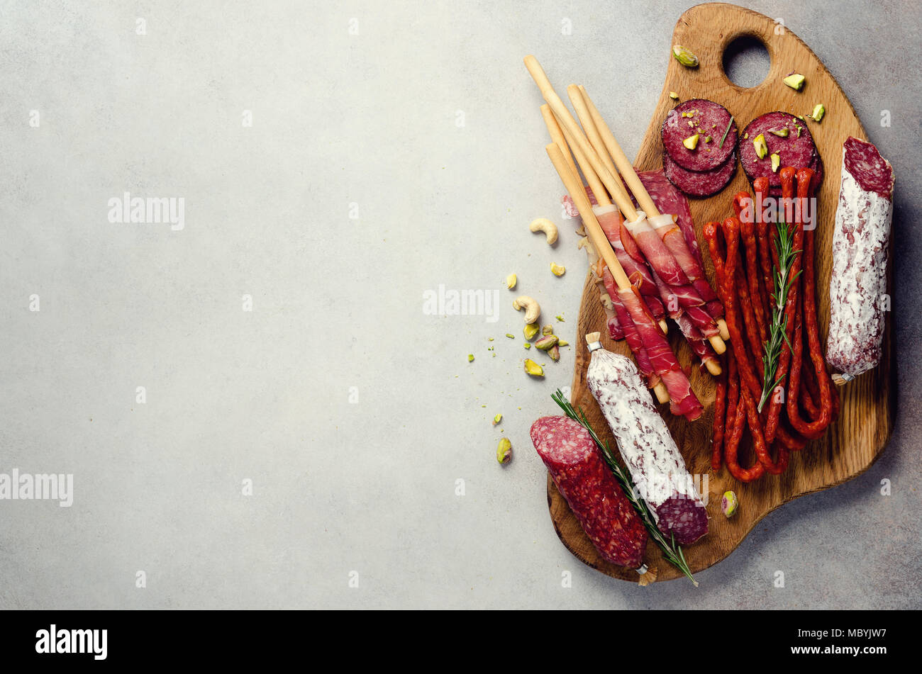 Antipasto plate with meat, olives, grissini bread sticks on grey concrete background. Top view, copy space, flat lay - Stock Image