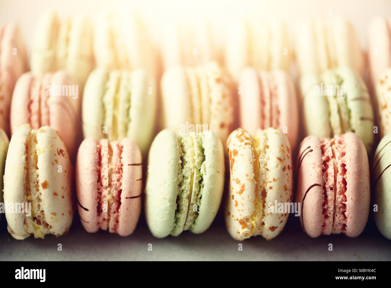 Colorful french macaroons flat lay. Pastel colors pink, green, yellow macarons with copy space, top view. Holidays and celebrations concept. Sweet gift for woman, girl - Stock Image