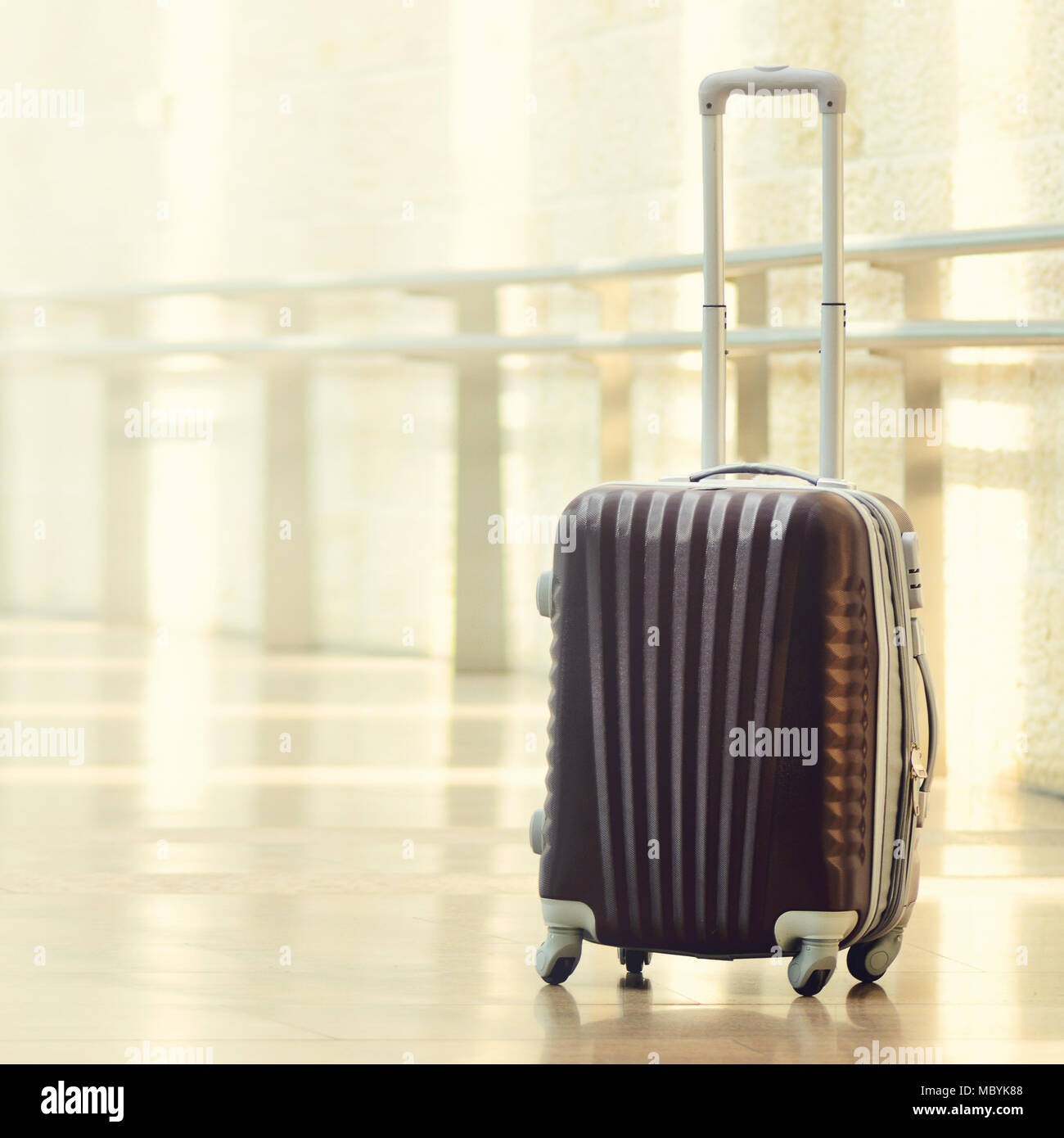 Packed travel suitcase, airport. Summer holiday and vacation concept. Traveler baggage, brown luggage in empty hall interior. Copy space. Square crop - Stock Image