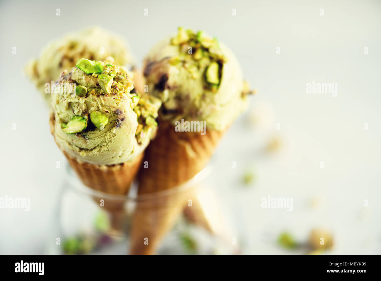 Green ice cream in waffle cone with chocolate and pistachio nuts on grey stone background. Summer food concept, copy space. Healthy gluten free ice-cream. - Stock Image