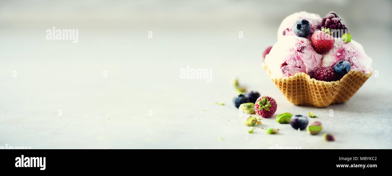Pink ice cream with berries, strawberries, blueberries, raspberries, pistachios in waffle basket. Summer food concept, copy space. Healthy gluten free fruit ice-cream. Banner - Stock Image
