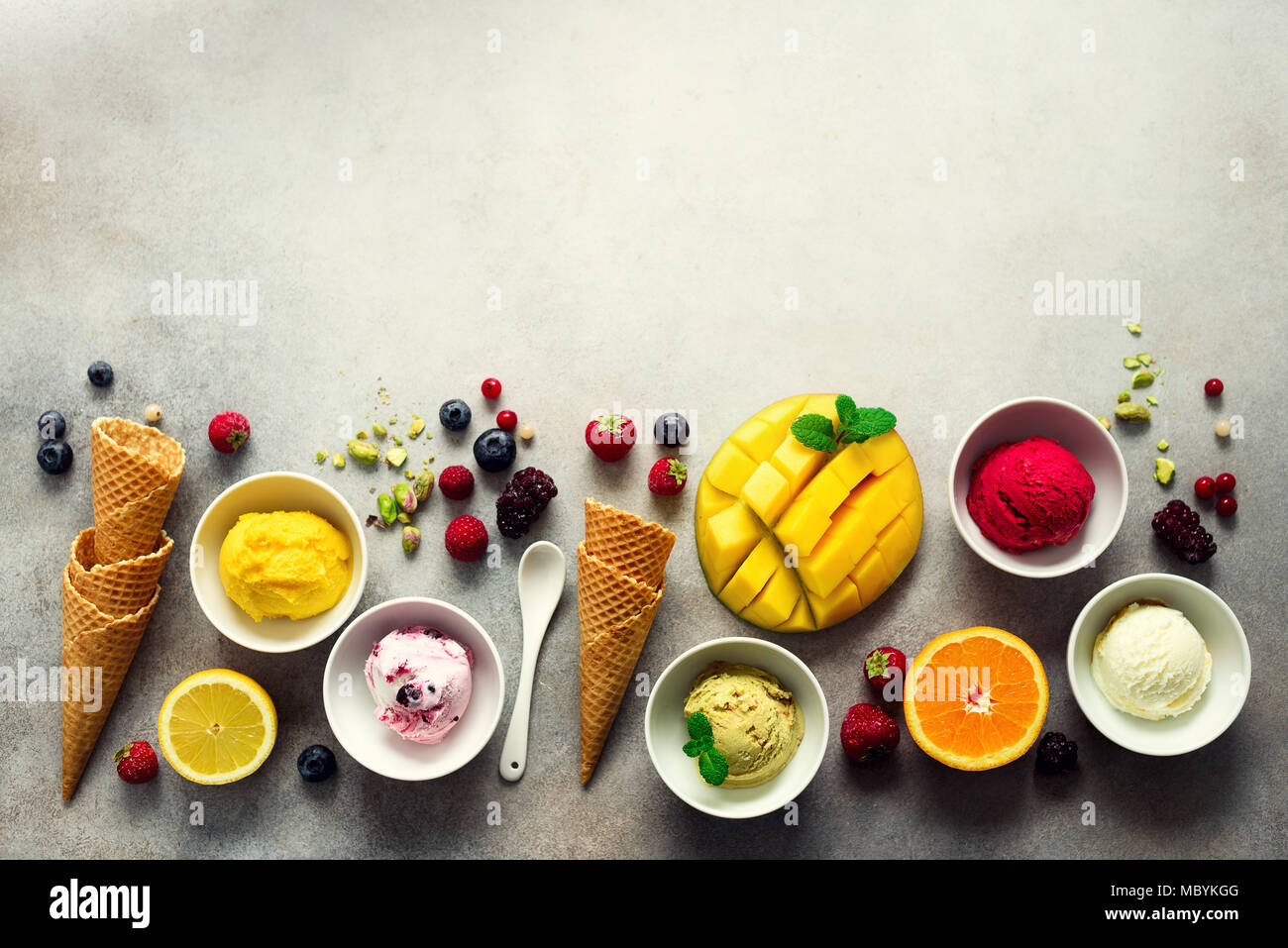 Ice cream balls in bowls, waffle cones, berries, orange, mango, pistachio on grey concrete background. Colorful collection, flat lay, summer concept, top view - Stock Image