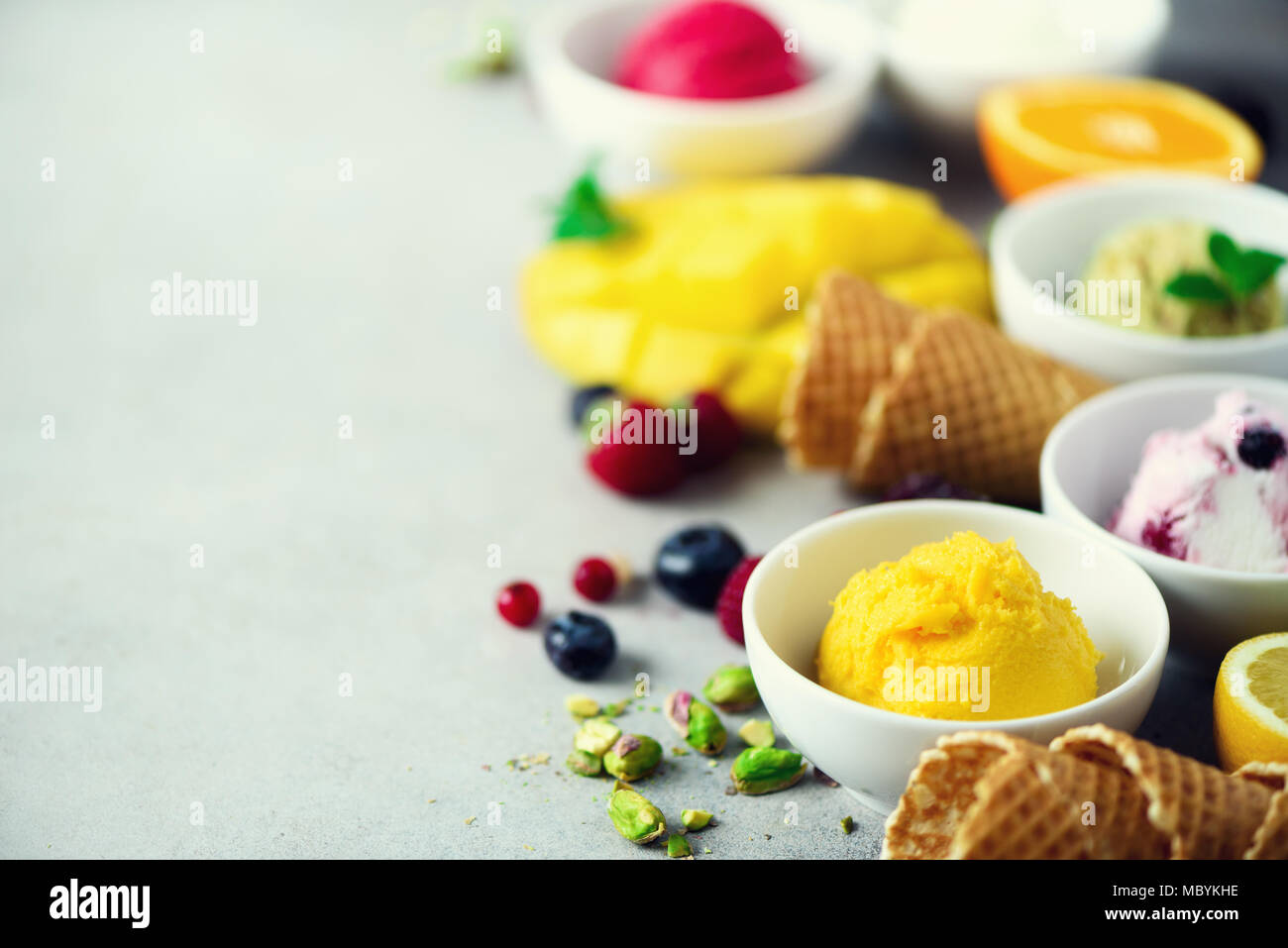 Ice cream balls in bowls, waffle cones, berries, orange, mango, pistachio on grey concrete background. Colorful collection, flat lay, summer concept - Stock Image