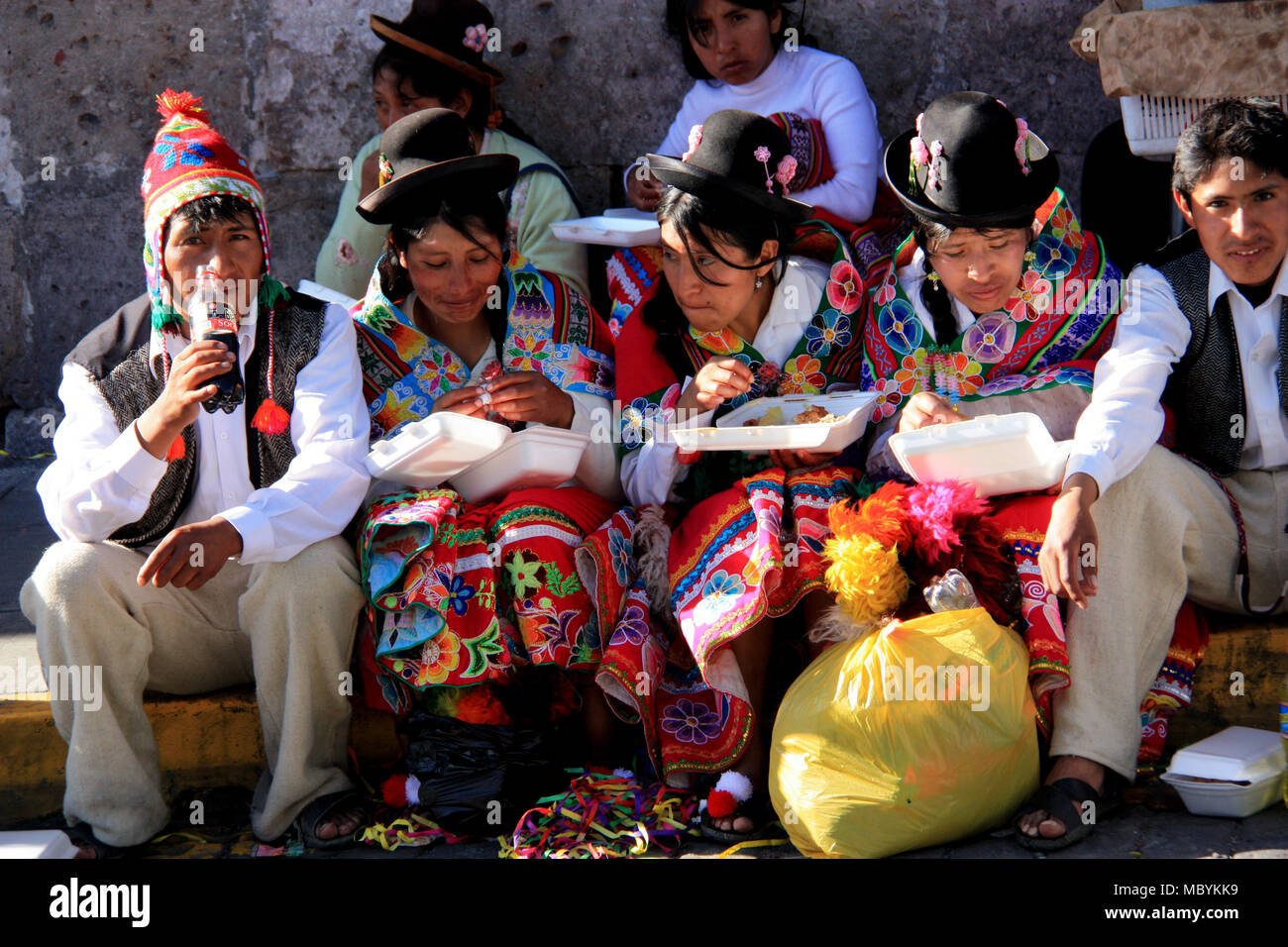 Traditionally dressed Peruvian Teenagers are sitting on the Side of the Street and eating, drinking and enjoying a Folklore Festival in Arequipa, Peru - Stock Image