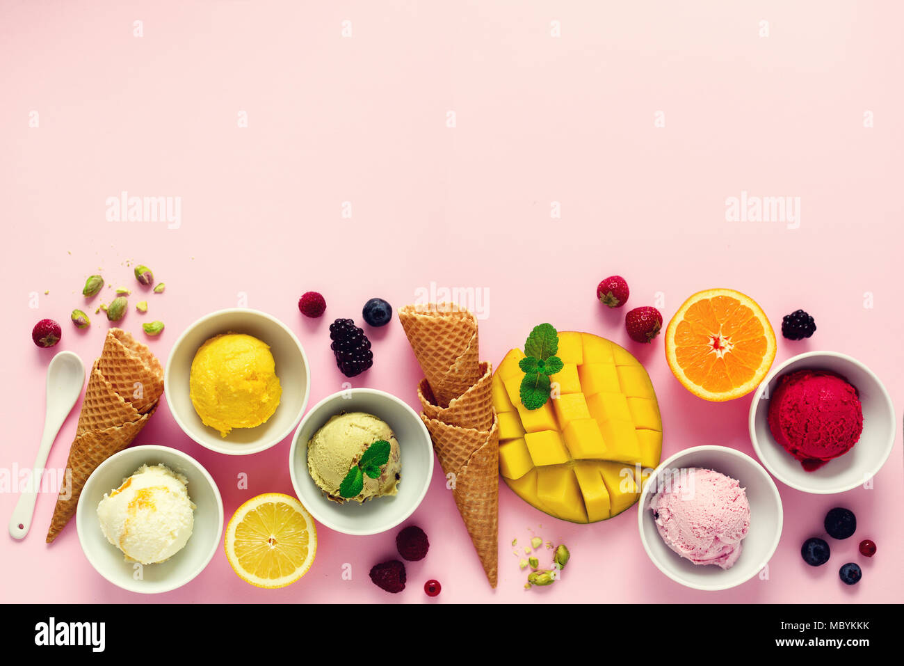 Ice cream balls in bowls, waffle cones, berries, orange, mango, pistachio on pink shabby chic background. Colorful collection, flat lay, summer concept, top view - Stock Image