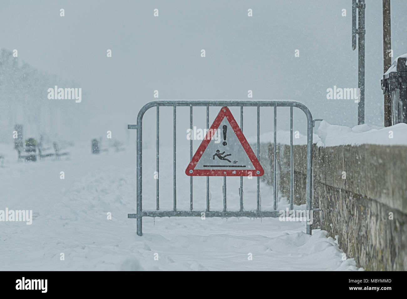 A red triangular road sign hanging at a gate on a pedestrian street signaling slippery attention due to snow. - Stock Image