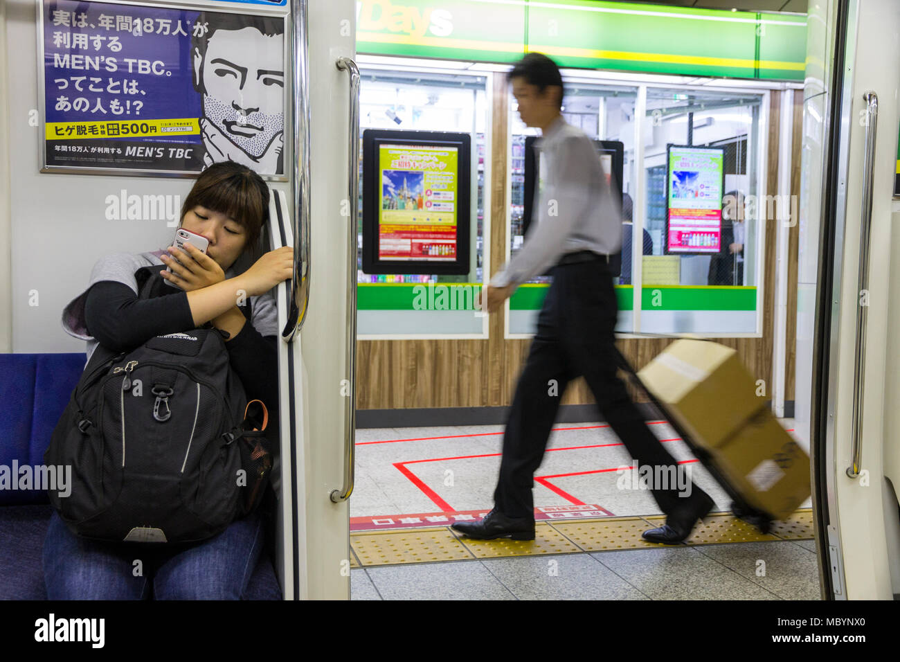 Tokyo, Japan. Typical scene at the Tokyo Subway, with a sit young girl looking at her mobile phone, an advertisement, and a delivery man in haste - Stock Image