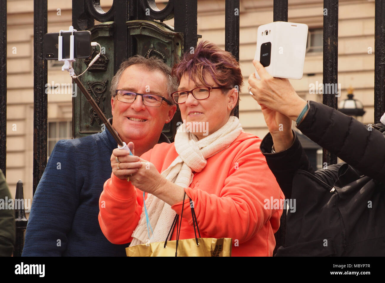 A middle aged couple, smiling, taking a selfie outside the front railings of Buckingham Palace with another man's hands taking another selfie - Stock Image