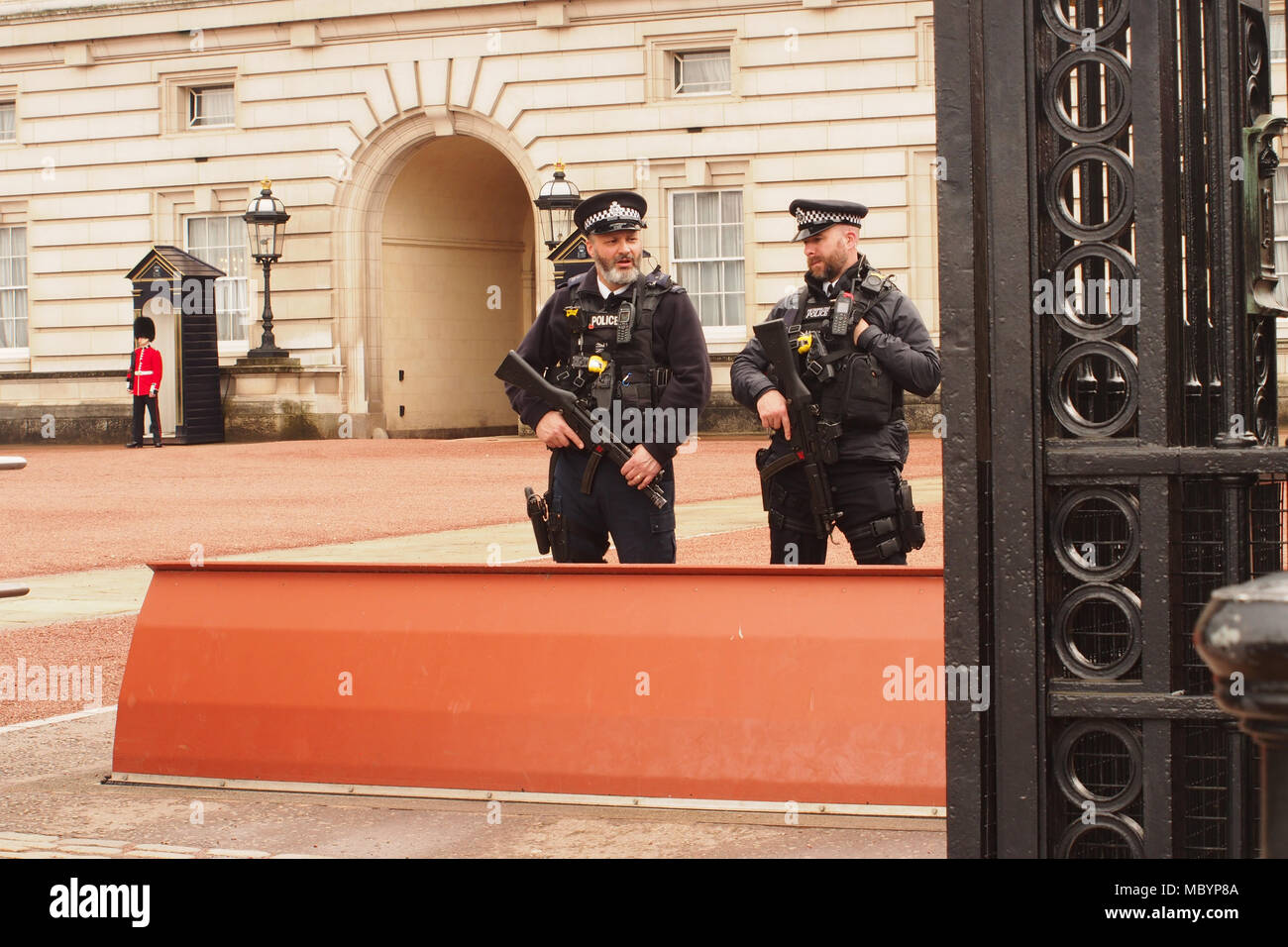 Two armed policemen at the road entrance to Buckingham Palace, London with one of the Queen's lifeguards in the background Stock Photo