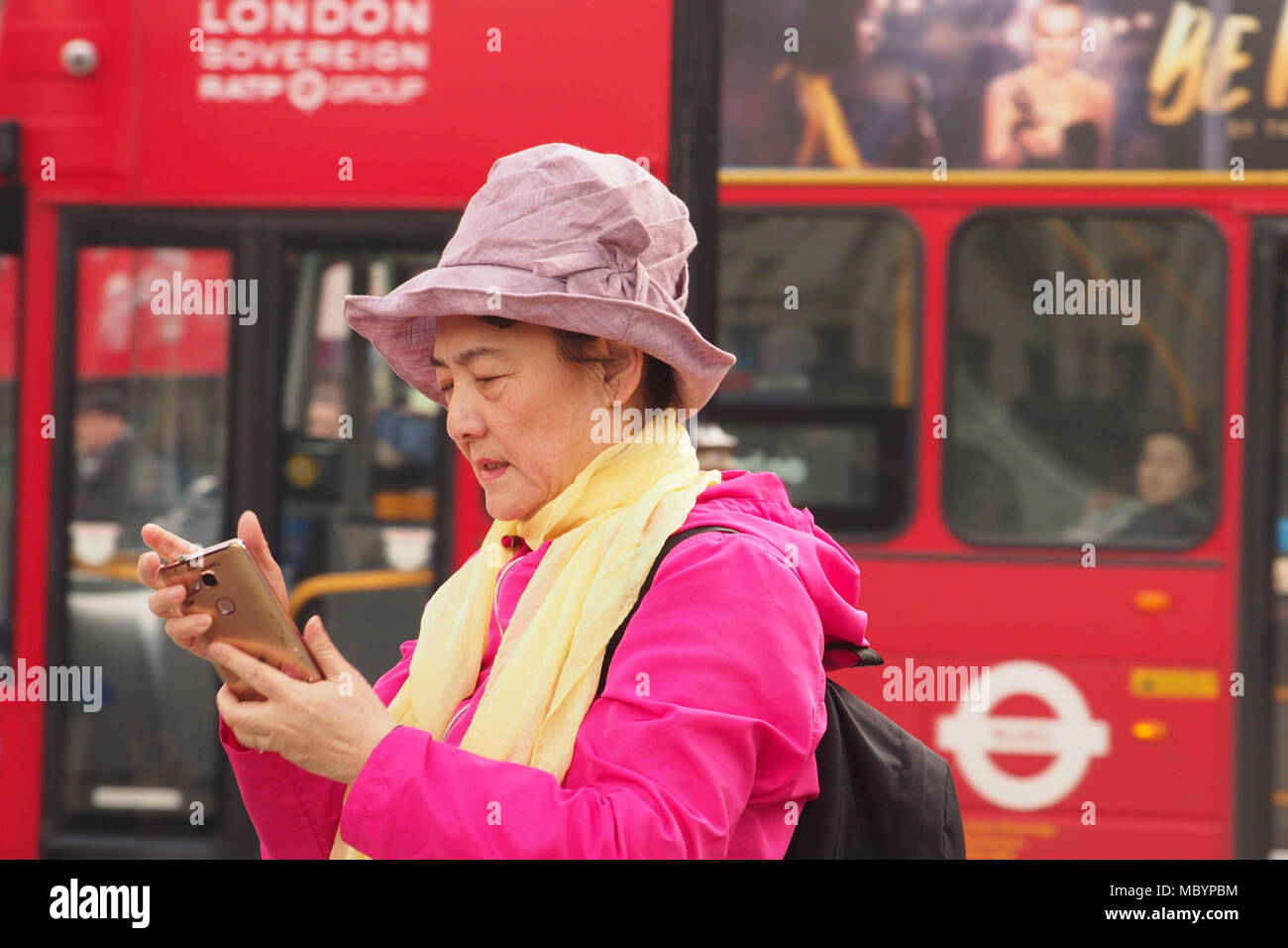 An older woman looking at her smartphone in Trafalgar Square, London wearing bright pink coat and hat and a yellow scarf with a bus in the background - Stock Image