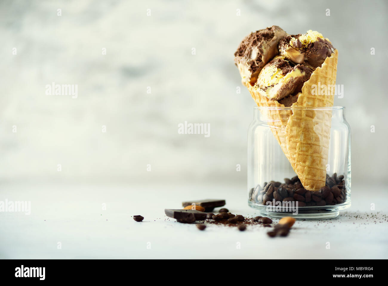 Chocolate and coffee ice cream in waffle cone with coffee beans on grey stone background. Summer food concept, copy space. Healthy gluten free ice-cream Stock Photo