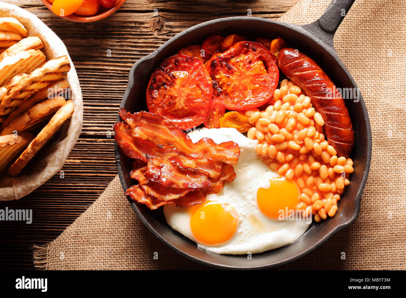 English Breakfast with sausages, grilled tomatoes, egg, bacon, beans and bread on frying pan. - Stock Image
