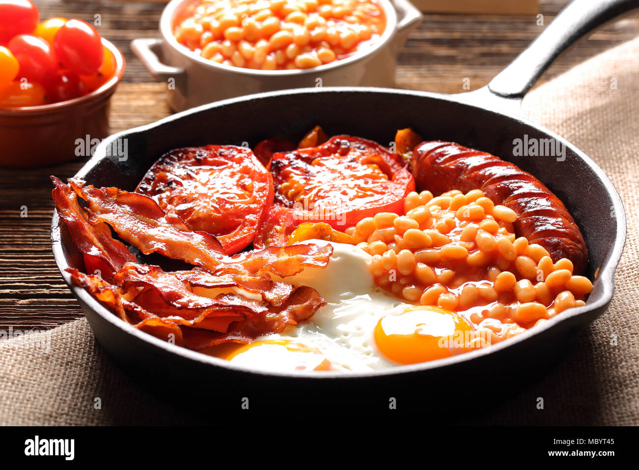 English Breakfast with sausages, grilled tomatoes, egg, bacon and beans on frying pan. Stock Photo