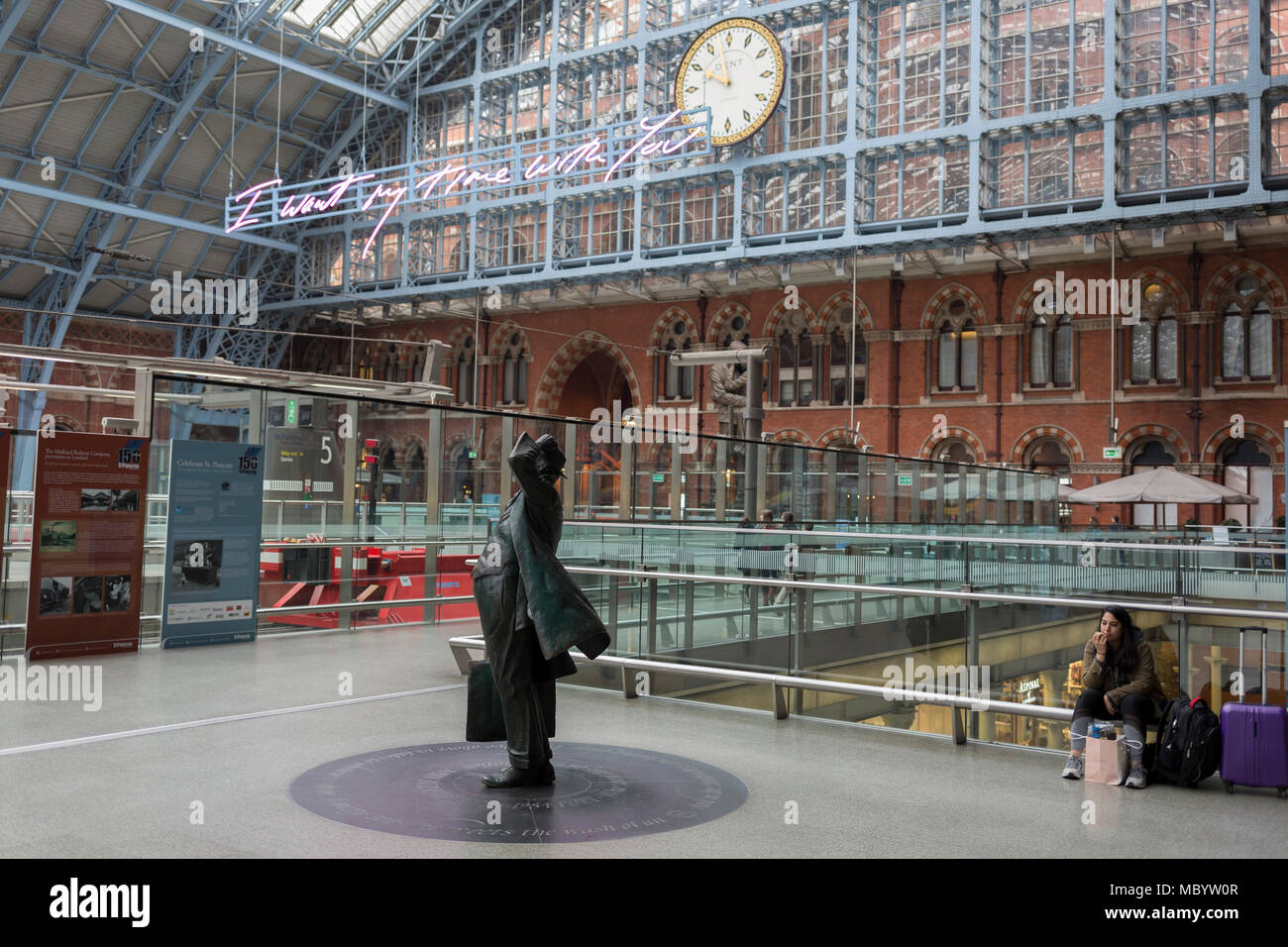 The statue of poet John Betjeman by Martin Jennings looks up to the new artwork entitled 'I Want My Time With You' by British (Britpop) artist Tracy Emin which hangs over the main concourse at St. Pancras Station, on 10th April 2018, in London, England. In the sixth year of the Terrace Wires Commission - and in celebration of the 150th anniversary of St Pancras International and the 250th anniversary of the Royal Academy of Arts, at one of London's mainline station, the London hub for Eurostar - the 20 metre-long greeting to commuters reads 'I Want My Time With You' and Emin thinks that arrivi - Stock Image