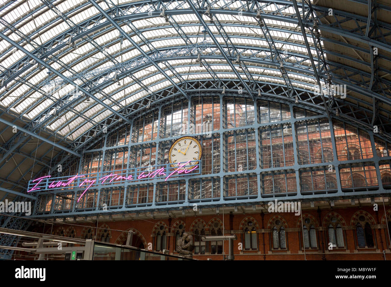 The new artwork entitled 'I Want My Time With You' by British (Britpop) artist Tracy Emin hangs over the main concourse at St. Pancras Station, on 10th April 2018, in London, England. In the sixth year of the Terrace Wires Commission - and in celebration of the 150th anniversary of St Pancras International and the 250th anniversary of the Royal Academy of Arts, at one of London's mainline station, the London hub for Eurostar - the 20 metre-long greeting to commuters reads 'I Want My Time With You' and Emin thinks that arriving by train and being met by a lover as they put their arms around the Stock Photo
