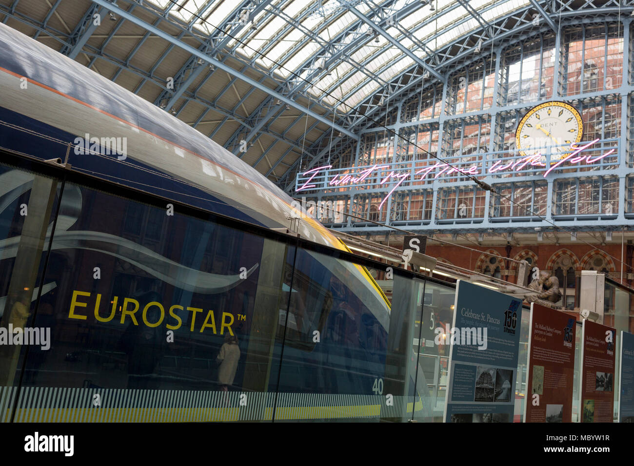 A Eurostar train and the new artwork entitled 'I Want My Time With You' by British (Britpop) artist Tracy Emin hangs over the main concourse at St. Pancras Station, on 10th April 2018, in London, England. In the sixth year of the Terrace Wires Commission - and in celebration of the 150th anniversary of St Pancras International and the 250th anniversary of the Royal Academy of Arts, at one of London's mainline station, the London hub for Eurostar - the 20 metre-long greeting to commuters reads 'I Want My Time With You' and Emin thinks that arriving by train and being met by a lover as they put  - Stock Image