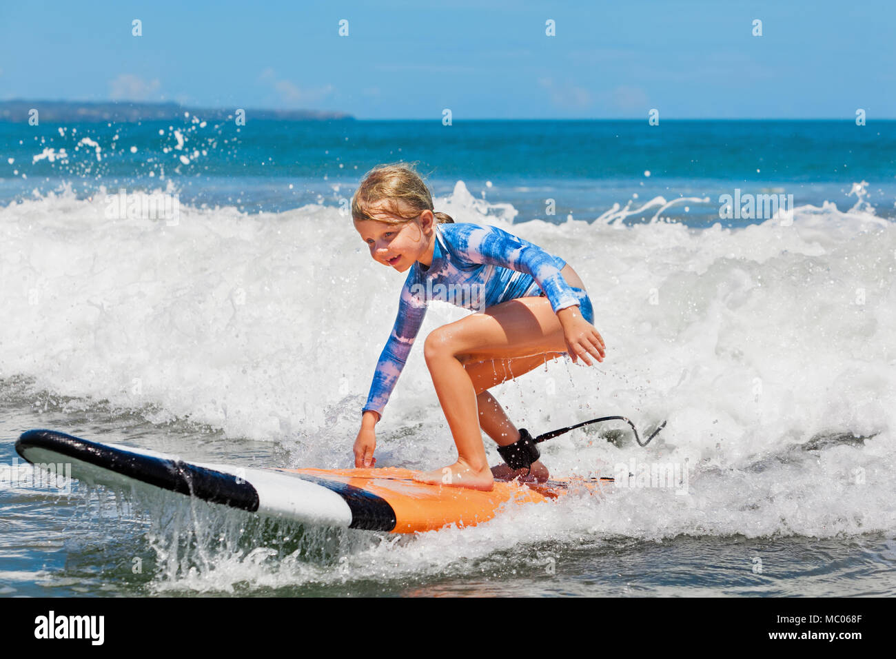 Happy baby girl - young surfer ride on surfboard with fun on sea wave Active family lifestyle, kids outdoor water sport lessons and beach activities - Stock Image