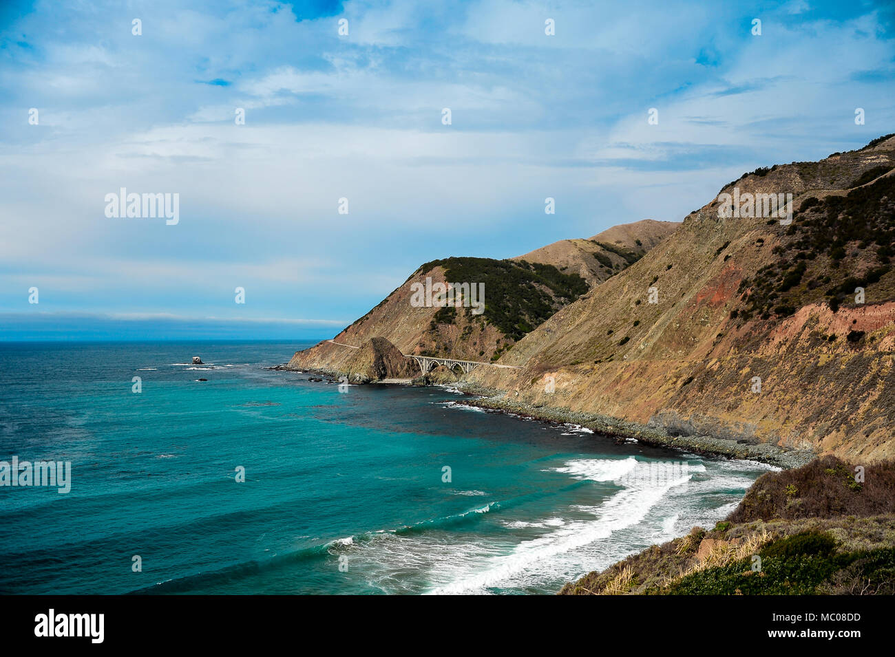 Pacific coast views along Cabrillo Highway to Big Creek Cove bridge, California. Beautiful landscape, cloudy skies, rocky cliffs and aquamarine sea. - Stock Image