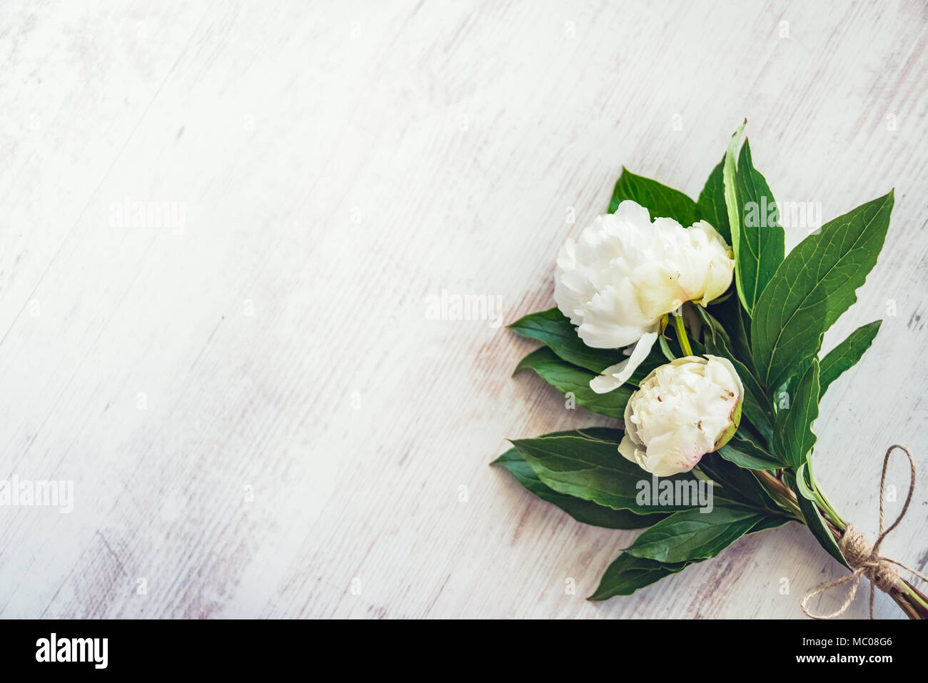 Top View Of A Bouquet Of White Peonies Flowers Over White Wooden