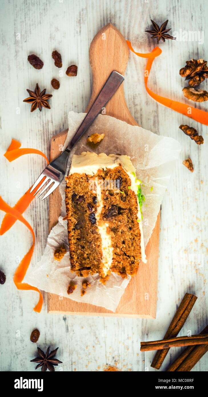 Top view of a homemade carrot cake with raisins, walnuts and cinnamon over white wooden background. Cream cheese frosting. - Stock Image
