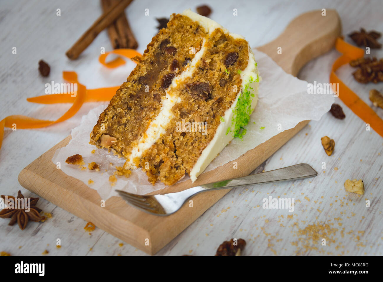 Close up of a homemade carrot cake with raisins, walnuts and cinnamon over white wooden background. Cream cheese frosting. - Stock Image