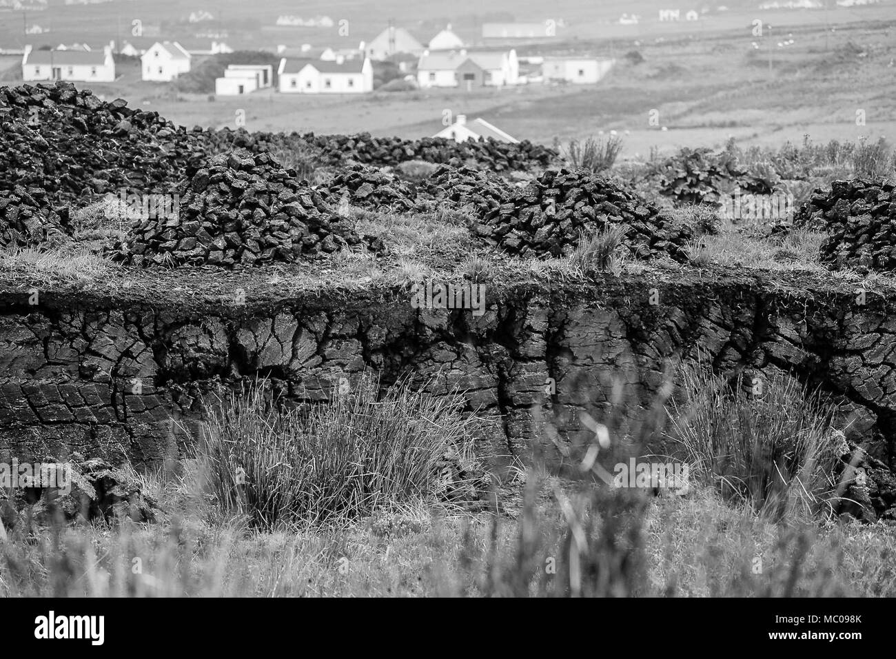 Black and white scene of peat bog with village background on Achill Island, County Mayo in Ireland. Horizontal of a peat cut, with turf  piles drying - Stock Image